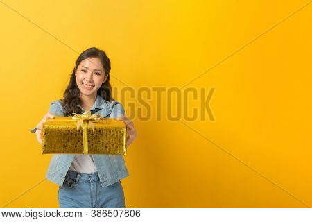 Happy Asian Pretty Woman In Casual Clothing Jeans Smiling And Hold New Year Gift Box Over Copy Space
