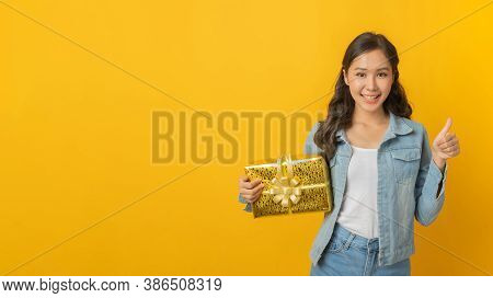 Happy Asian Pretty Woman In Casual Clothing Smiling Showing Thumbs Up Hand And Hold New Year Gift Bo