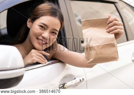 Asian Young adult in car holding disposable bag for take out food from drive thru service restaurant. Drive thru is new normal and popular service after coronavirus covid-19 pandemic.