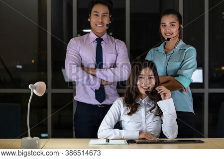 Late Night Environment, Portrait of friendly Call centre operator team with headsets in a call center customer service and technical support. Using for 24 Hr. Call center Concept.