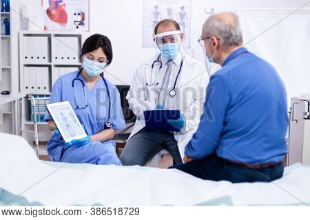 Doctor Telling Senior Man He Is Suffering Of Osteoporosis During Medical Check In Hospital Room Wear