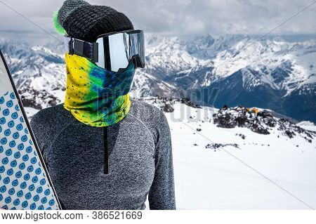 A Slender Skier In A Ski Mask And A Headscarf Stands In The Mountains. Holds Skis Against The Backgr