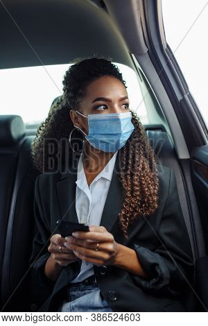 Young Business Woman In A Mask Checking Her Mobile Cell Phone On A Backseat Of A Taxi During Covid-1