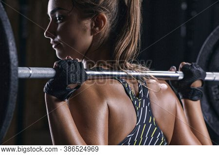 Cropped Conceptual Inspiration Lifestyle Photo Of Female Fitness Model With A Barbell On Her Shoulde