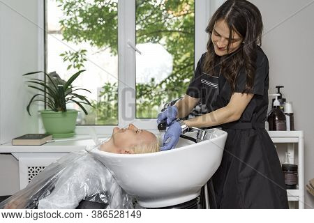 Hairdresser Washes Off Lightener From Hair Of Young Woman In Beauty Salon