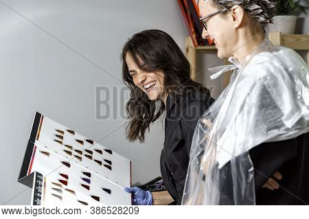 Cute Beautiful Hairdresser Laughs And Helps Young Woman Choose A Shade Of Color From The Palette. Co