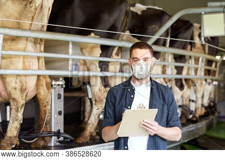 agriculture industry, farming, people, milking and animal husbandry concept - young man or farmer with clipboard and cows at rotary parlour system on dairy farm wearing mask for protection from virus