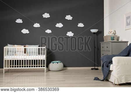 Cute Baby Room Interior With Modern Crib Near Decorative Clouds On Dark Wall