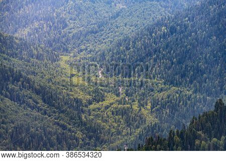 The Landscape Of The Taiga Of Gorny Altai, With A Slight Haze, Cedars And A River Flowing In The Low