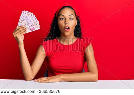 Young african american girl holding mexican pesos sitting on the table scared and amazed with open mouth for surprise, disbelief face