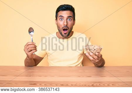 Young handsome hispanic man eating healthy whole grain celears sitting on the table afraid and shocked with surprise and amazed expression, fear and excited face.
