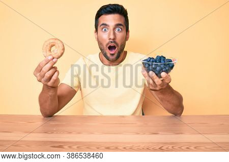 Young hispanic man eating breakfast holding donut and blueberries afraid and shocked with surprise and amazed expression, fear and excited face.
