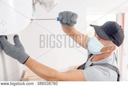 Technician Man In Medical Mask Worker Repairing And Installs Air Conditioner On White Wall