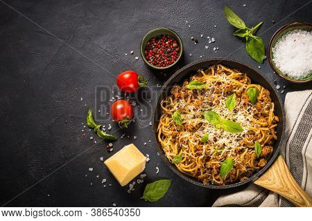 Pasta Bolognese, Meat Ragout In Tomato Sauce. Traditional Italian Dish In The Skillet At Black Table