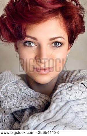 Portrait Of A Beautiful Young Red-haired Woman With Short Hair Wearing Warm Woolen Sweater Looking A