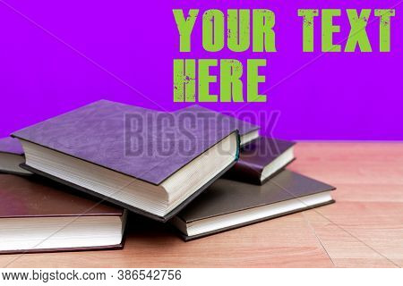 A Few Books On Wooden Deck Table And Mild Purple Background