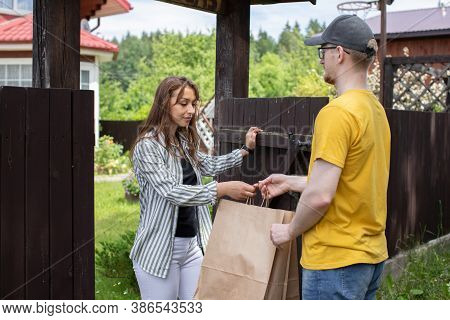 Uniformed Delivery Man Courier Handing Paper Bag Of Food To Customer By Gate Of Country House In Ope