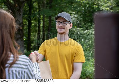 Uniformed Delivery Man Courier Handing Paper Bag Of Food To Customer In Open Air At Natural Green Ba