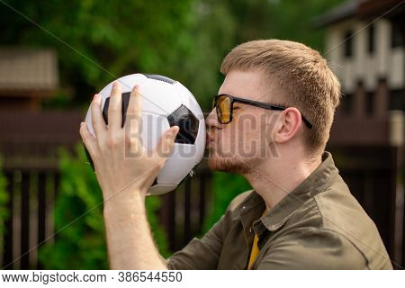 Happy Male Football Fan Kisses Soccer Ball, Young Man Support Sport Team, Celebrating Victory. Peopl