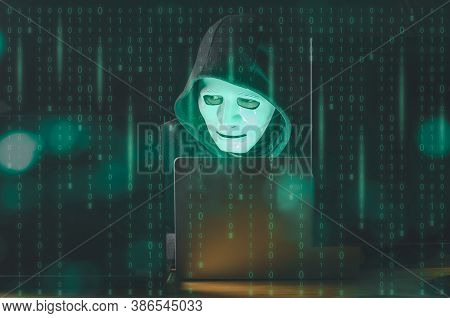 Hacker And Malware Concept. Dangerous Hooded Hacker Man Using Laptop With Binary Code Digital Interf