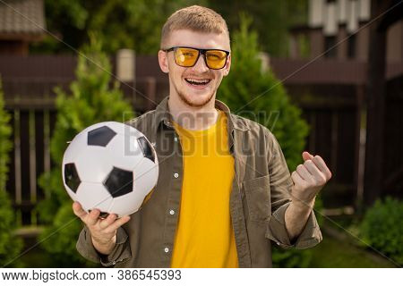 Excited Young Man With Soccer Ball Smiling, Happy Male Football Fan Support Sport Team, Celebrating