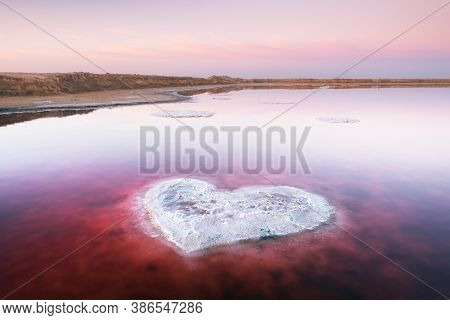 Heart from salt in pink water salt lake in Ukraine, Europe. Creative concept
