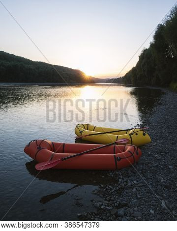 Orange and yellow packrafts rubber boats with padles on a sunrise river. Packrafting. Active lifestile concept