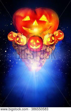 Halloween pumpkin in dark night sky. Concept of jack-o-lantern pumkin tornado up in bright star burst background.