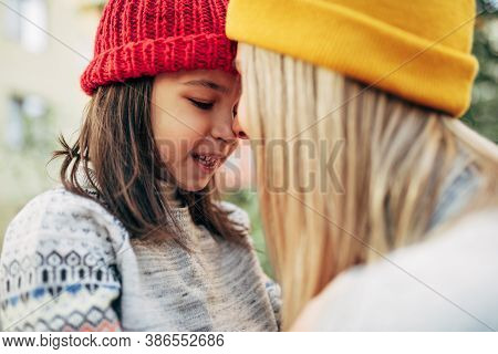 Closeup Image Of Happy Little Girl In Red Cap Hugging Her Mom In Yellow Cap. Cute Kid Embracing Her