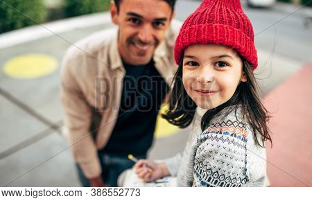 Cute Little Girl In Red Cap Is Sitting Outdoor And Drawing With Her Dad. Father Enjoying The Time To