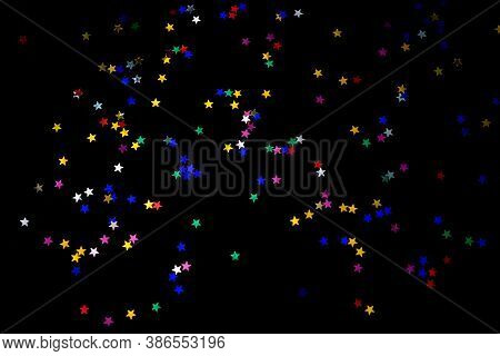Multi-colored Stars On A Black Background. Festive Background Of Colorful Confetti Stars On A Black