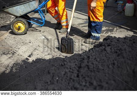 Asphalt Laying. A Worker Repairs The Road. The Road Service Is Laying The Road Surface. Replacing Th