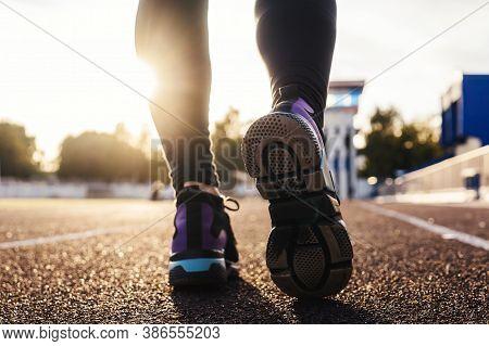 Runner Feet Running On Stadium Tracks Closeup On Shoe. Woman Fitness Sunset Jog Workout Welness Conc
