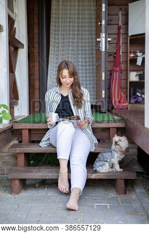 Young Beautiful Woman Resting Outdoors With Cup Of Coffee, Reading Morning Press On Porch Of Country