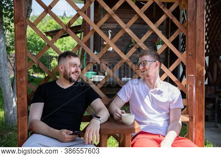 Happy Smiling Male Friends Resting Outdoors, Two Handsome Guys Sitting On Back Yard Of Coutry House,