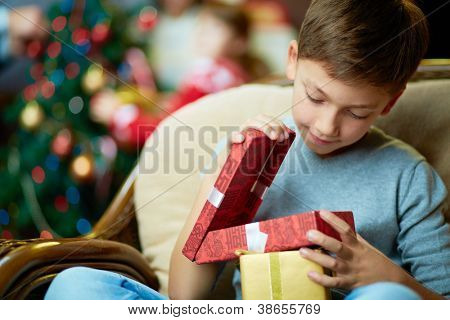 Portrait of adorable boy with giftboxes looking into one of them