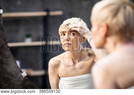Skin Anti-wrinkle Treatment. Unhappy Middle-aged Woman Looking At Wrinkles Touching Face Standing In