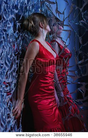 beautiful woman looking at the broken mirror