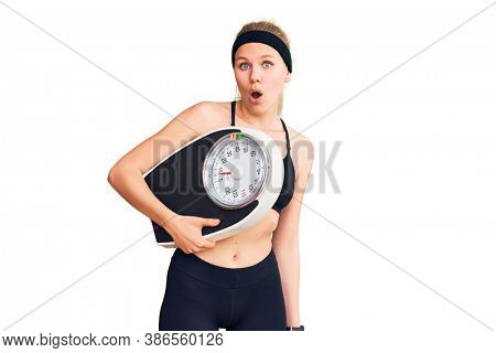 Young beautiful blonde woman wearing sportswear holding weighing machine scared and amazed with open mouth for surprise, disbelief face