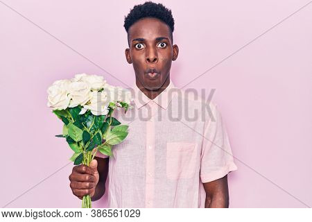 Young african american man holding flowers scared and amazed with open mouth for surprise, disbelief face