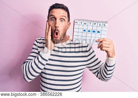 Young handsome man holding weather calendar showing rainy week over pink background scared and amazed with open mouth for surprise, disbelief face