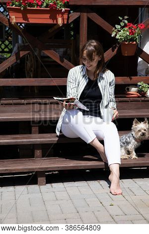 Cool Fashionable Young Brunette Woman Smiling Reading Magazine With York Dog On Wooden Cottage Terra