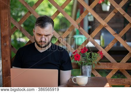 Handsome Young Man Wearing Black T-shirt Works With Laptop On Background Of Wooden Pergola Grid. Dis
