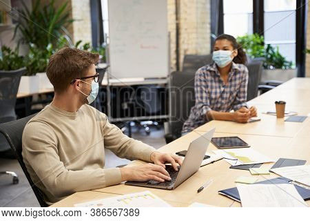 Two Young Coworkers Wearing Medical Protective Masks Sitting Together At The Table In The Modern Off