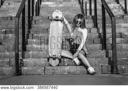 Black-white Portrait Of A Young Woman Sitting On A Skateboard