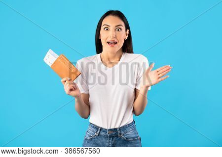 Cheap Flights Concept. Portrait Of Surprised Shocked Woman Holding Passport And Boarding Pass Ticket