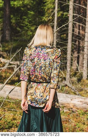 Blonde Woman With Colorful Blouse And Green Dress Walking In The Dense And Dark Forest