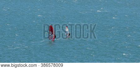 Portland Harbour, United Kingdom - July 2, 2020: High Angle Aerial Panoramic Shot Of Two Sail Boards