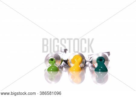 Three Squeezed Acrylic Paint Tubes Green, Light Green And Yellow Colours Reflected In Glass Table Su