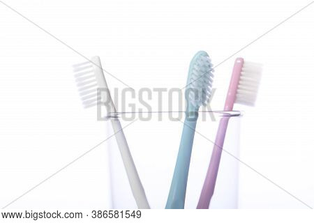 Close Up View Of Three Toothbrushes In Transparent Glass Isolated On White Background. Oral Care, Pe